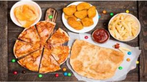 pizza, pastel, catchup, nuggets, fritas e balas dispostas sobre a mesa